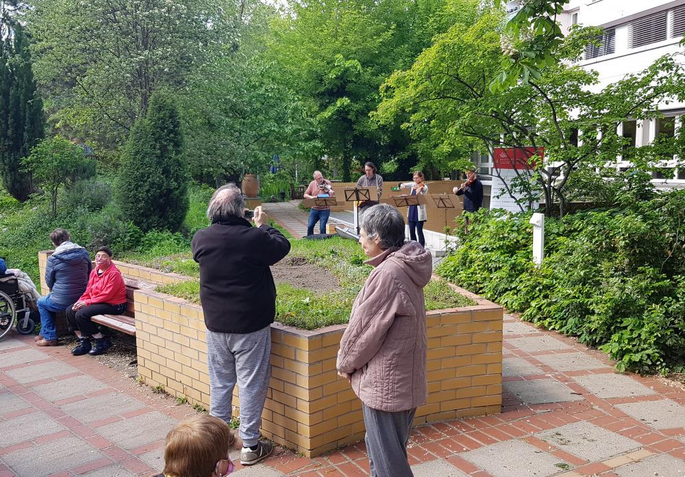 """Bewohner*innen und Nachbarn der """"Schrippenkirche"""" freuen sich über das Konzert"""